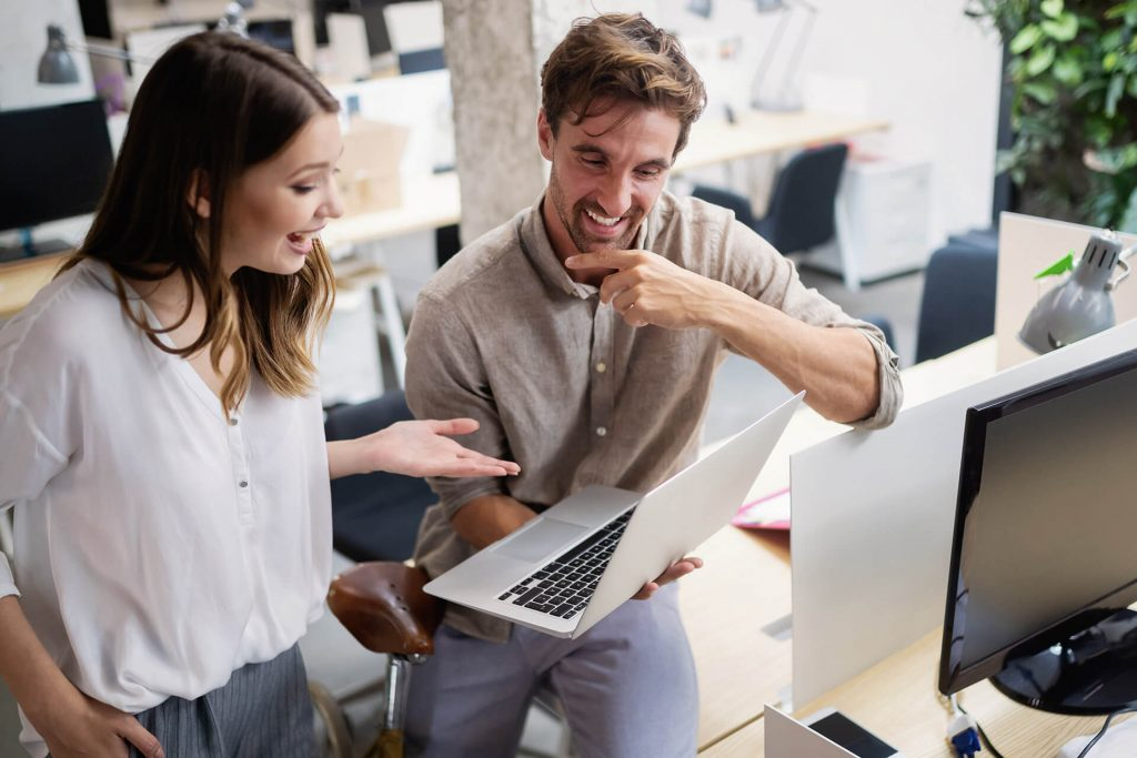 Zu sehen ist eine Frau und ein Mann, die gemeinsam am Laptop arbeiten.