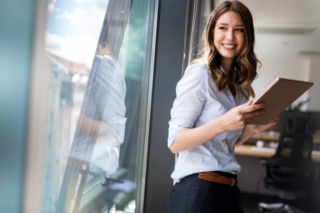 Eine Frau mit einem Tablet in der Hand steht am Fenster ihres Büros
