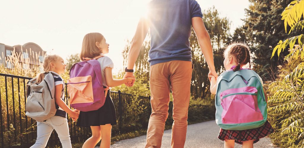 Ein Mann begleitet seine 3 Kinder zur Schule